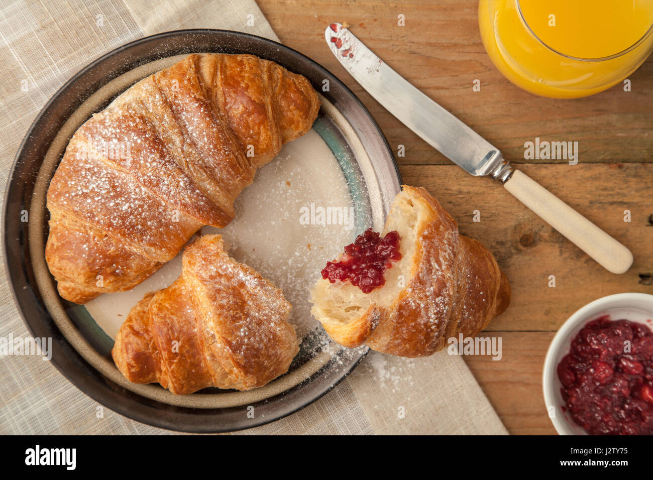 Top view of fresh croissants on a breakfast table settin - Stock Image