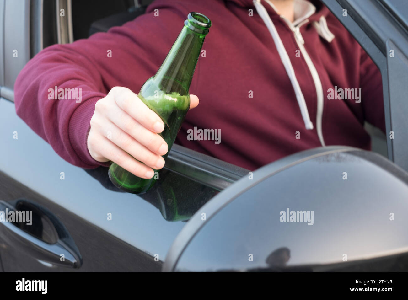 Drunk man driving his car and drinking alcohol - Stock Image