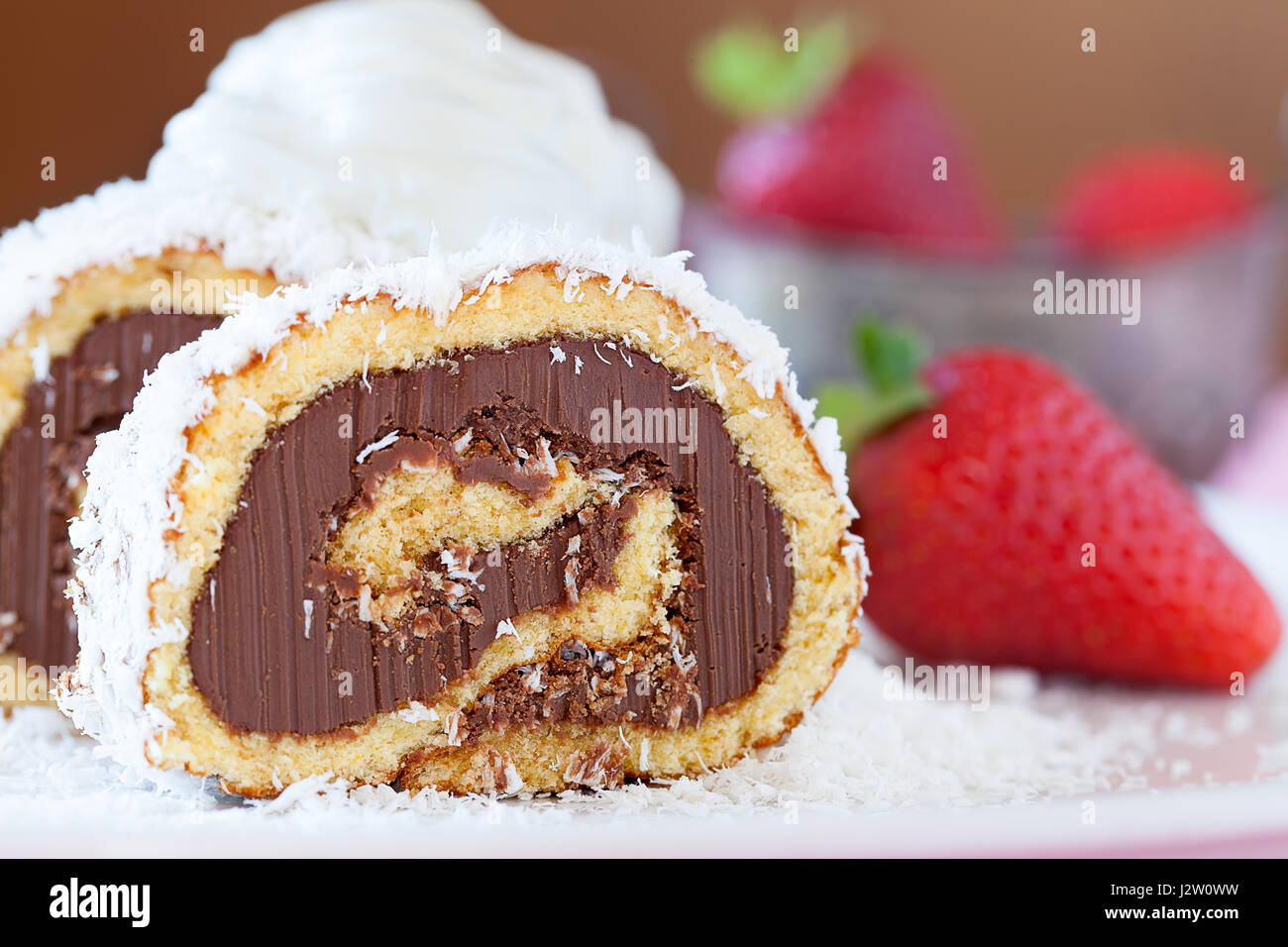 Slice of chocolate coconut cake roll decorated with ehipped cream and strawberries, closeup view. Stock Photo