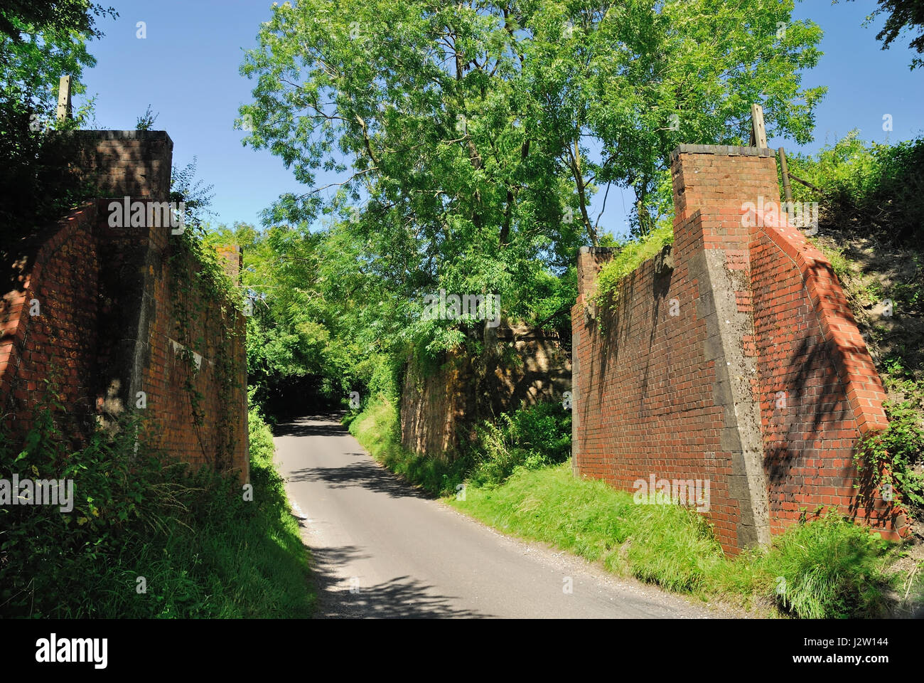 The supporting walls of two former railway bridges over a minor road. - Stock Image