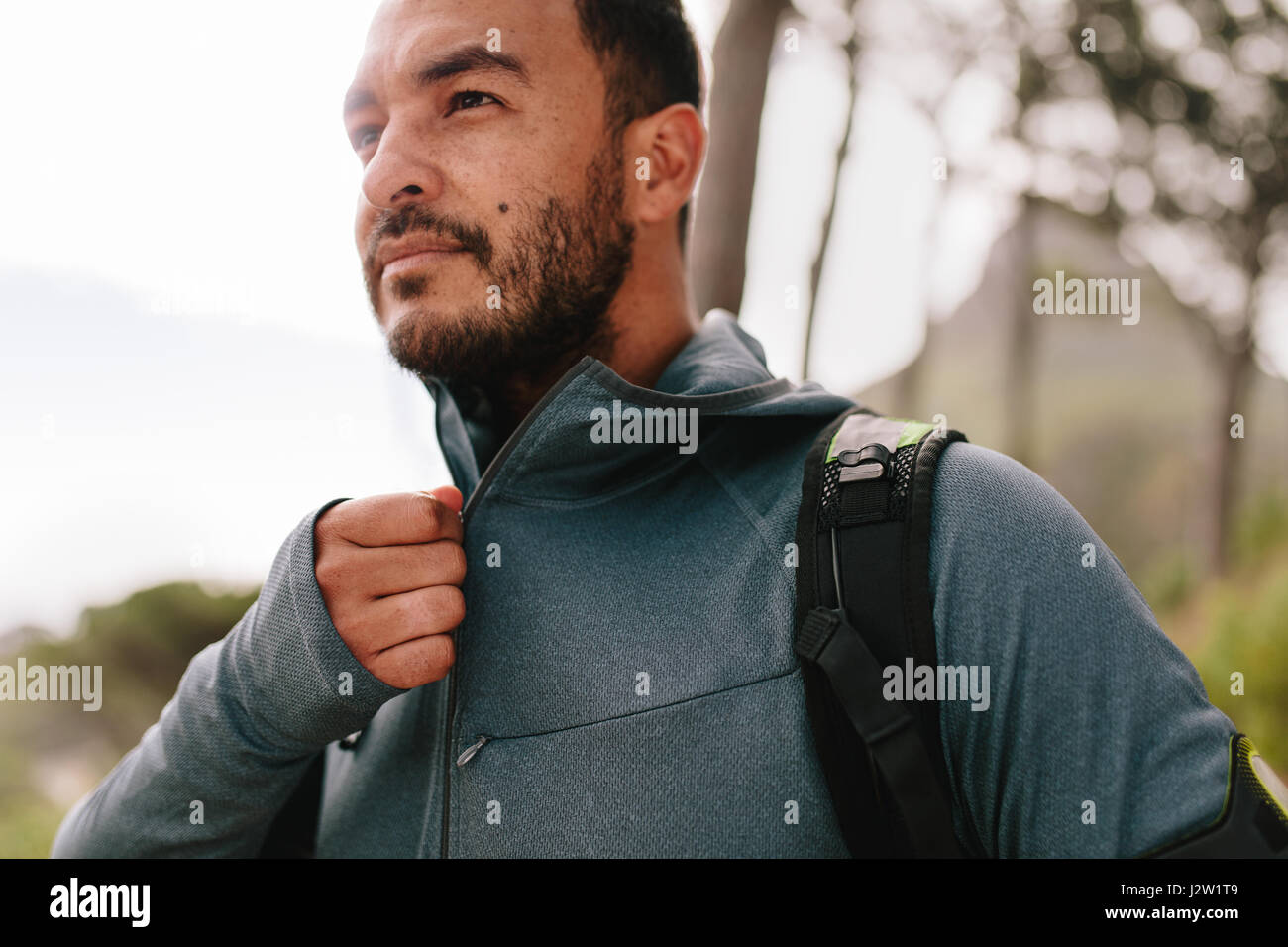 Portrait of healthy young man standing outdoors and looking away.  Handsome young male runner in sportswear. - Stock Image