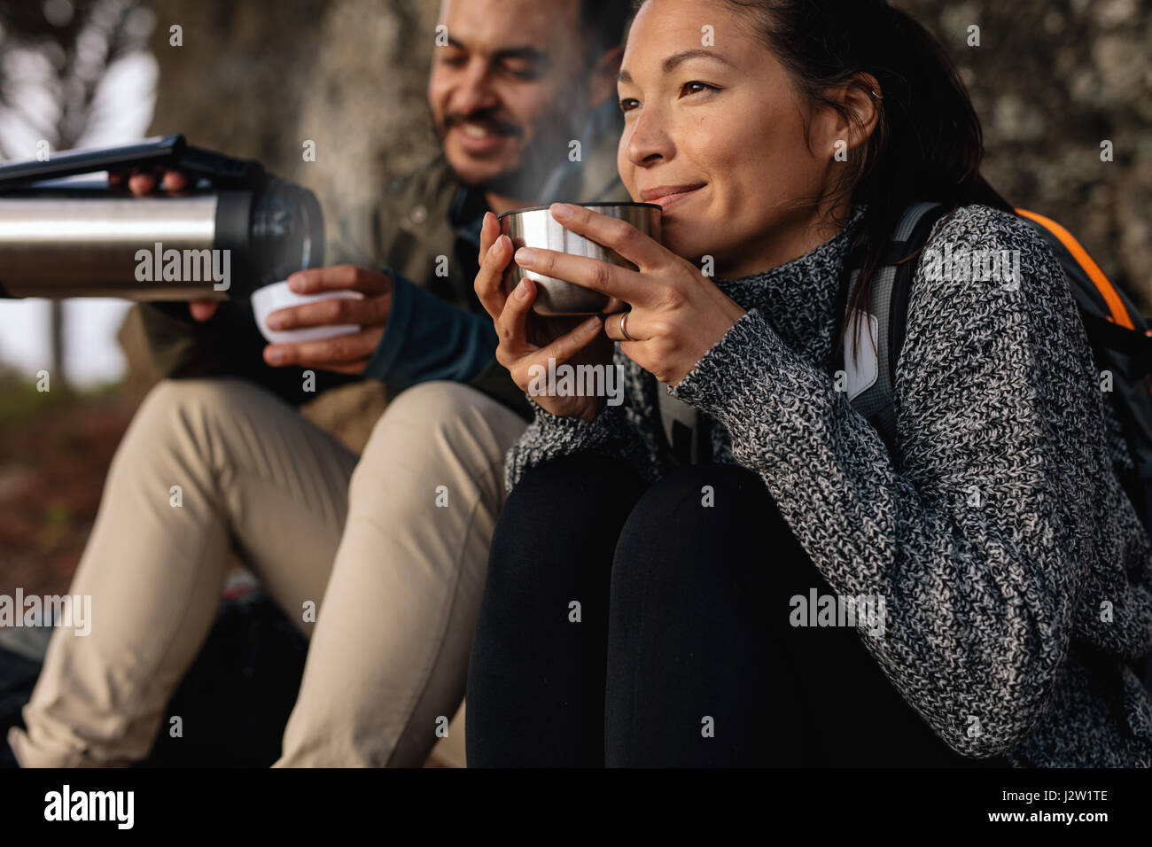 Young couple taking a break on a hike. Man and woman drinking coffee while out hiking. - Stock Image