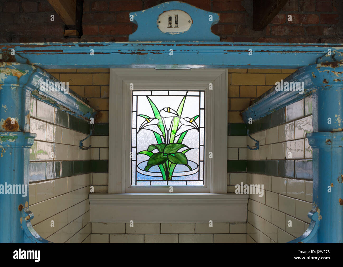 A modern stained glass window in an Edwardian changing cubicle, Victoria Baths, Manchester, England - Stock Image