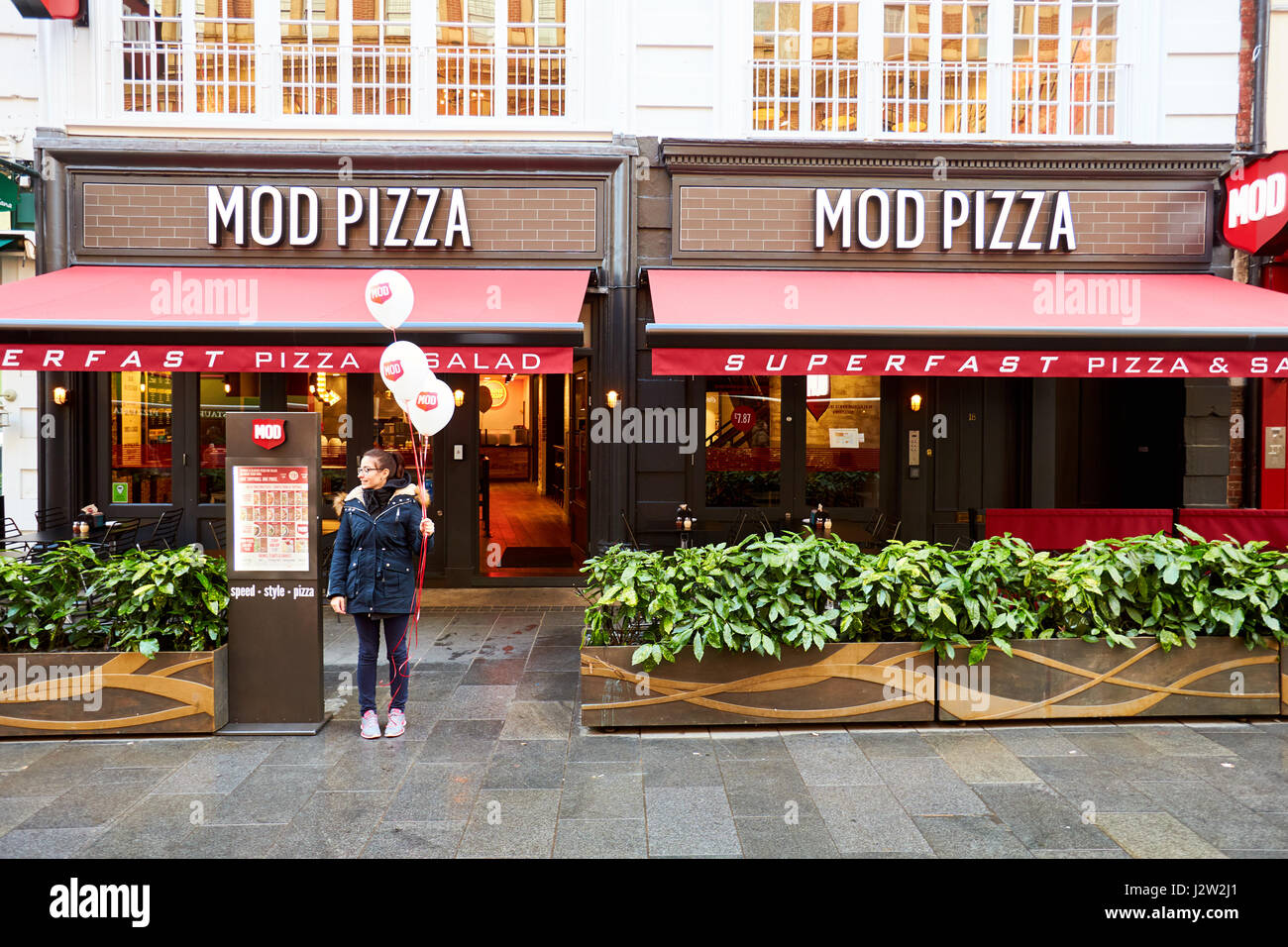 A Woman Stands Outside Mod Pizza Restaurant In London Stock