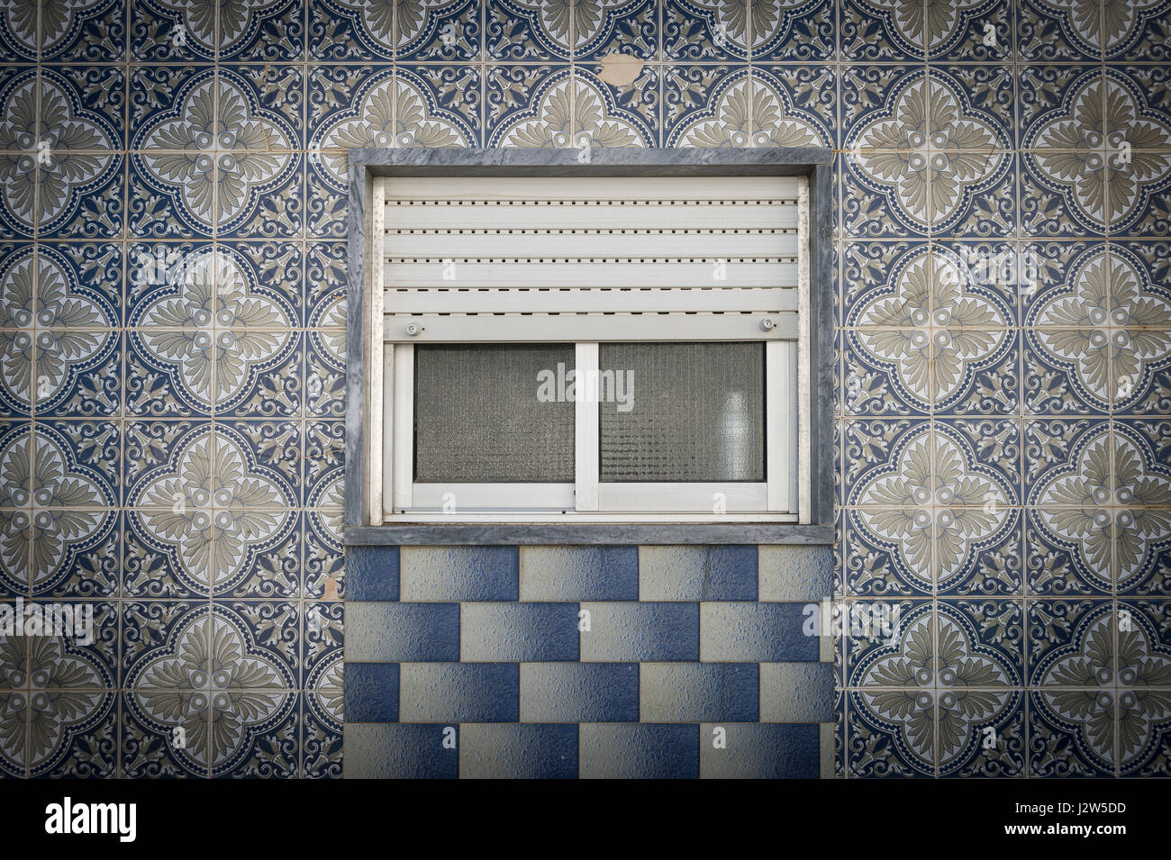 Portuguese ceramic tiles in geometric patterns on the outside of a portuguese ceramic tiles in geometric patterns on the outside of a building with a shuttered window dailygadgetfo Gallery