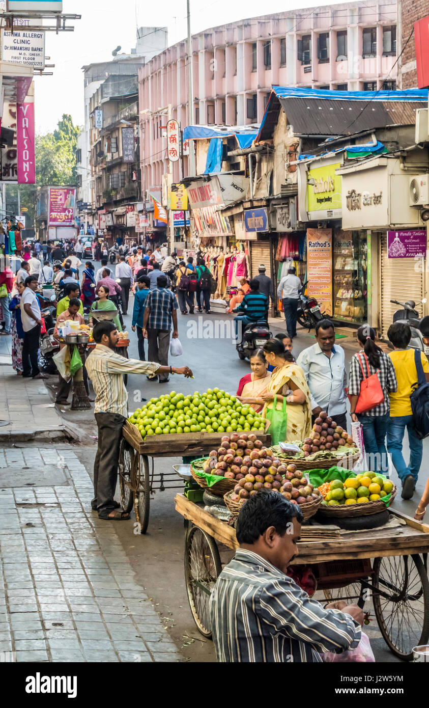 A street scene in Pune, India with people selling produce from carts. - Stock Image