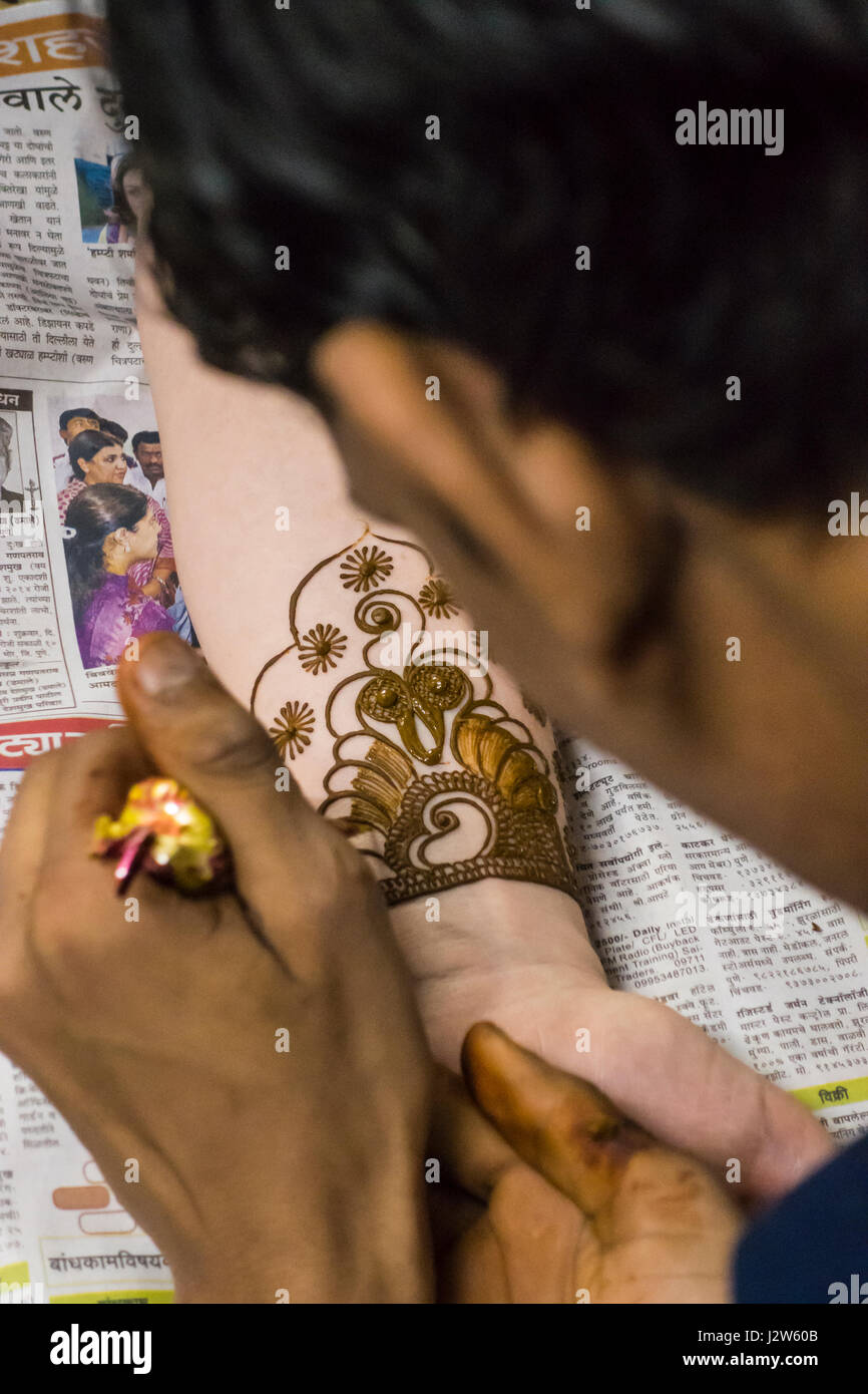 A Henna / Mehndi artist working on a bride's arm during a Henna party. - Stock Image