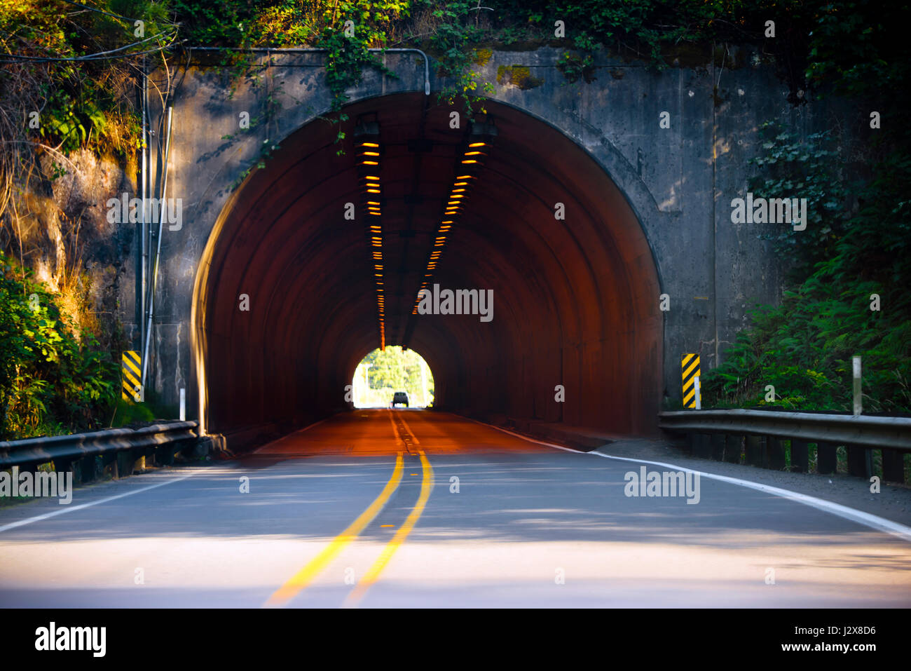 A road with a dividing strip for the opposing traffic flows pass through a long semi-circular concrete tunnel carved - Stock Image