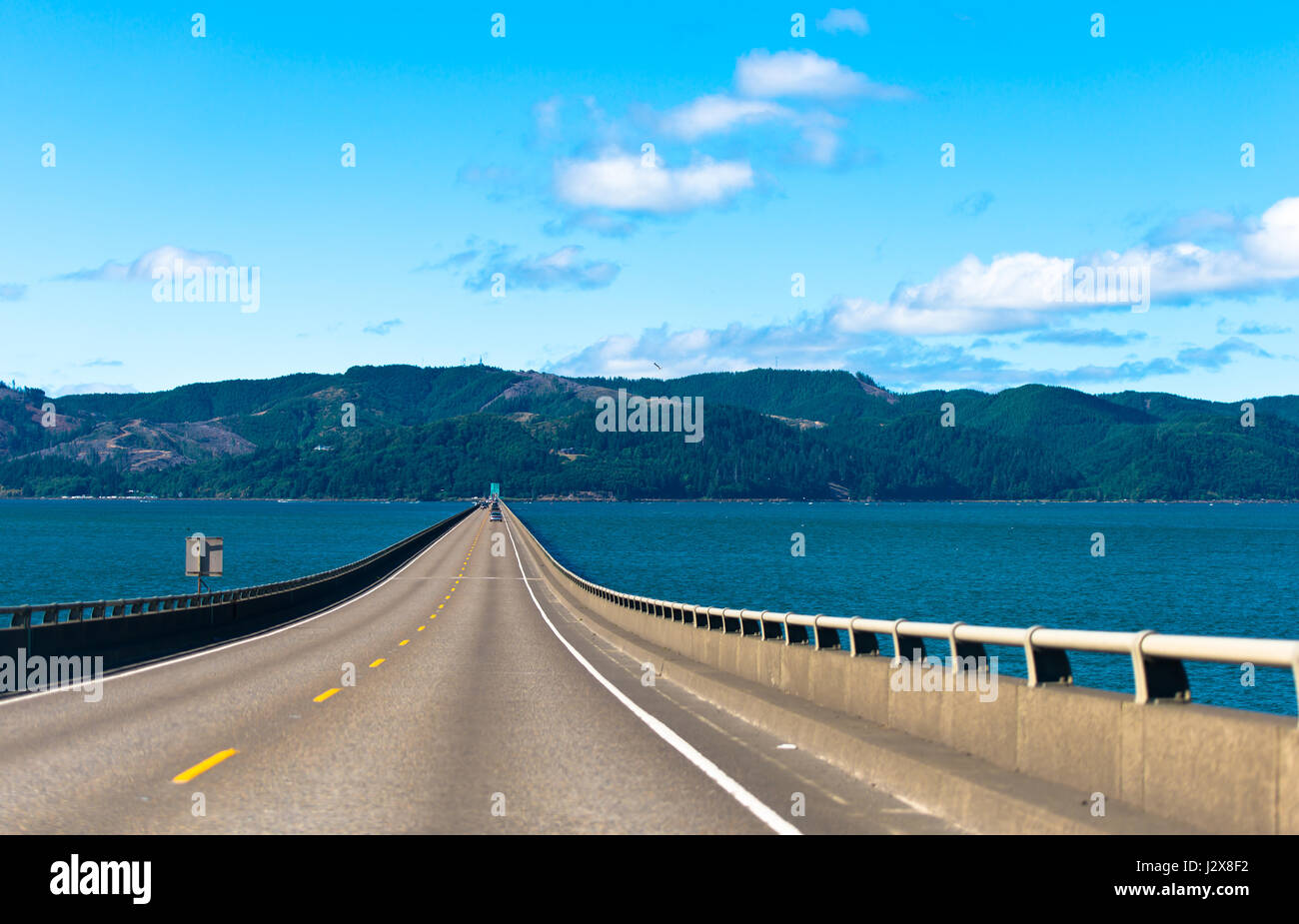 Long scenic road bridge with several lanes with raised sections and fencing in wide mouth of the Columbia River - Stock Image