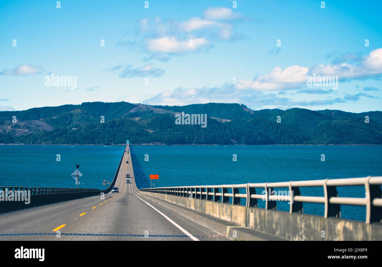 Long spectacular road bridge with several lanes with raised sections and fencing in wide mouth of the Columbia River - Stock Image