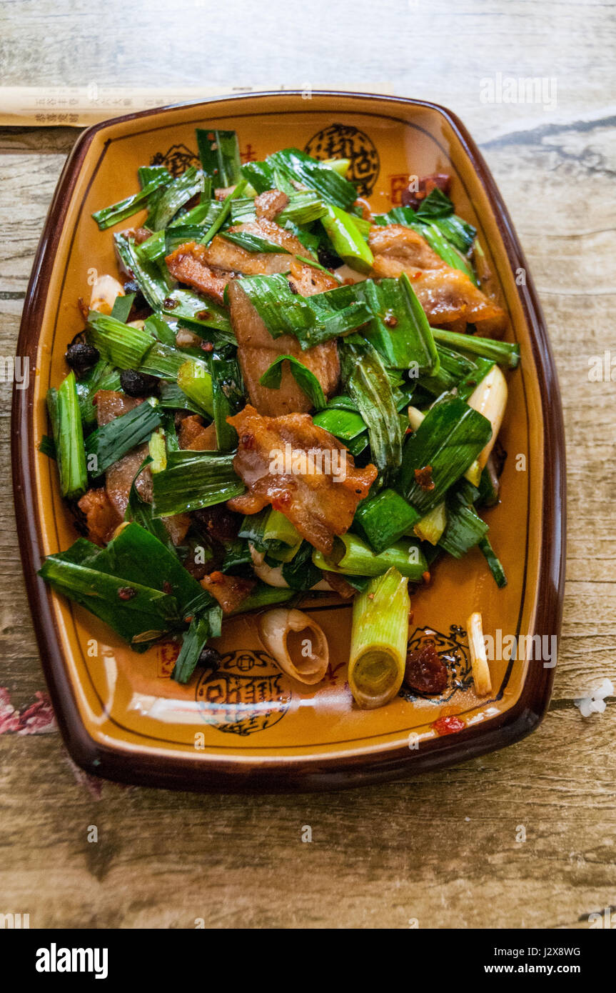 A dish of huiguo rou (twice cooked pork). Genuine Sichuan food at a roadside restaurant near Me'erkang Sichuan - Stock Image
