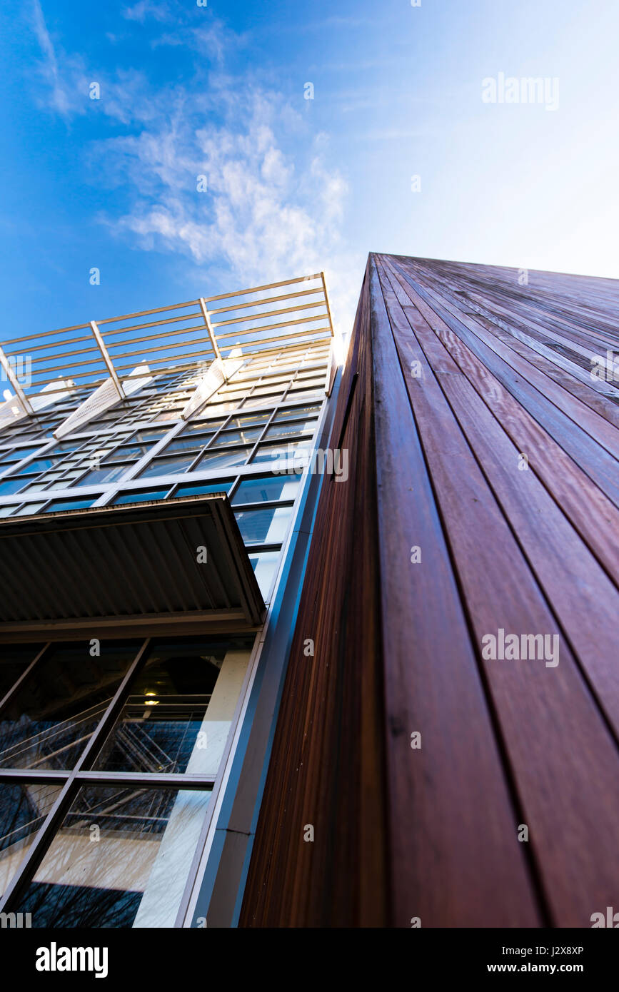 Architectural fragments of two buildings, one is made of mahogany wood planks, and the other of metal structures - Stock Image