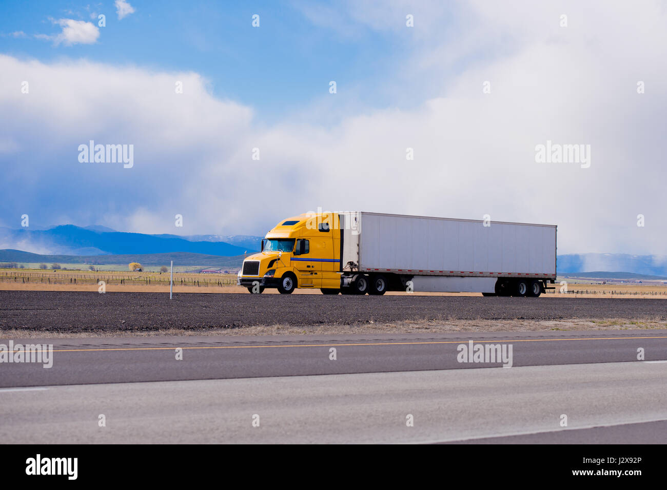 Classic modern semi truck bright yellow color with a white full length trailer aerodynamic skirts on a flat highway - Stock Image