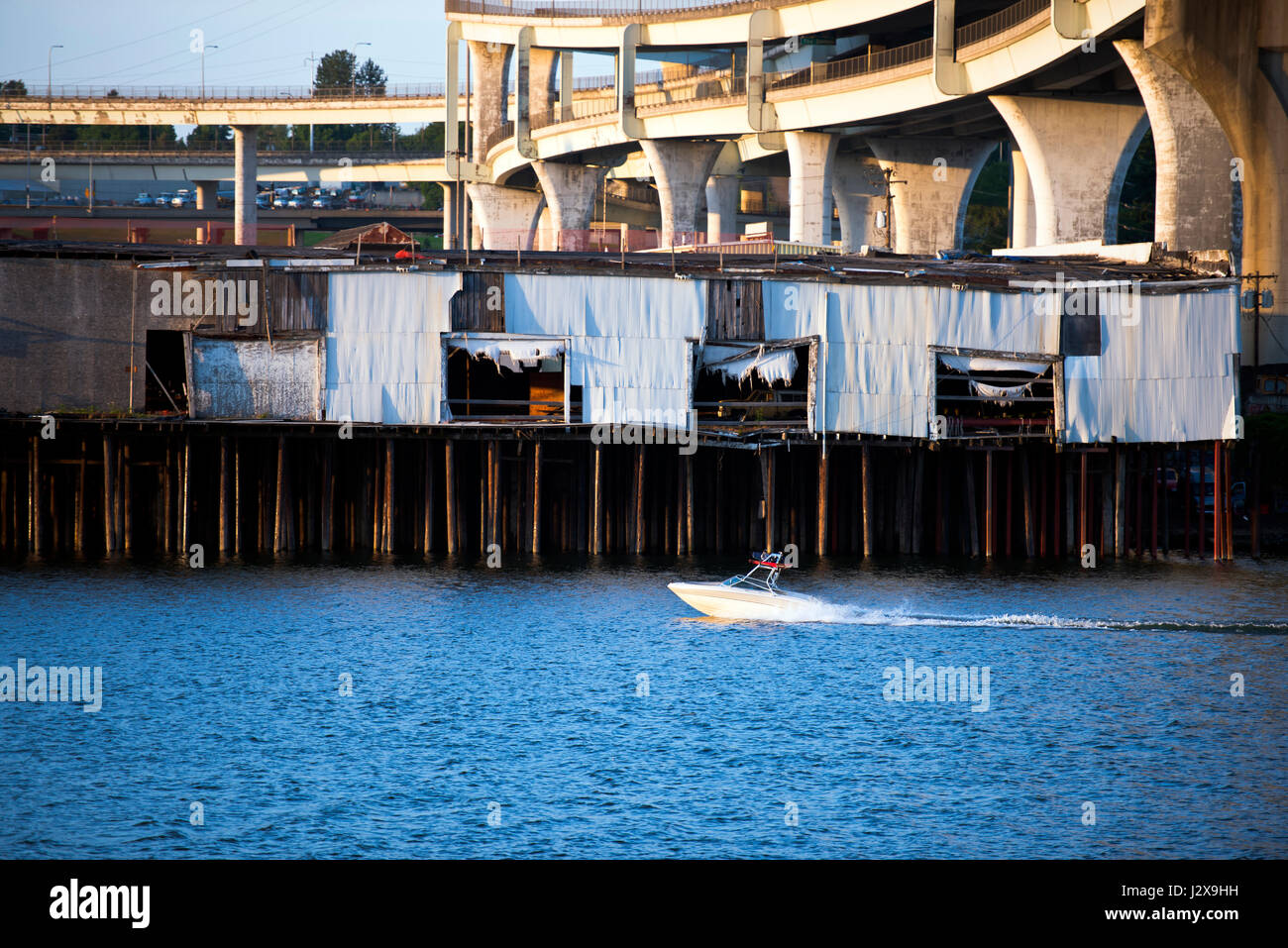 Motorboat on the Willamette River passes by the old docks with wooden props and white textile panels under the winding - Stock Image