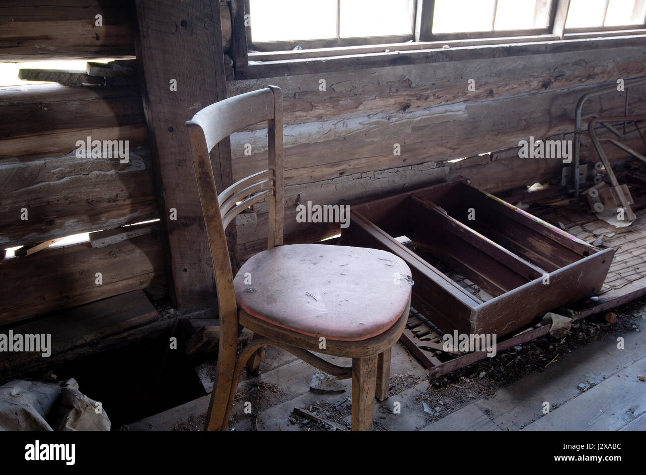 Old chair in an old house on a background of a wooden wall and window, next to which are located in the interior - Stock Image