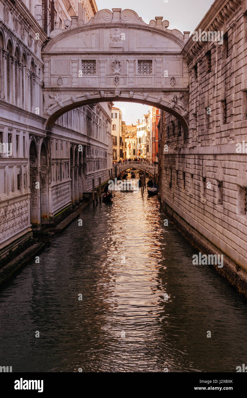 The famous Bridge of Sighs bathed in orange light at sunset in Venice, Italy Stock Photo