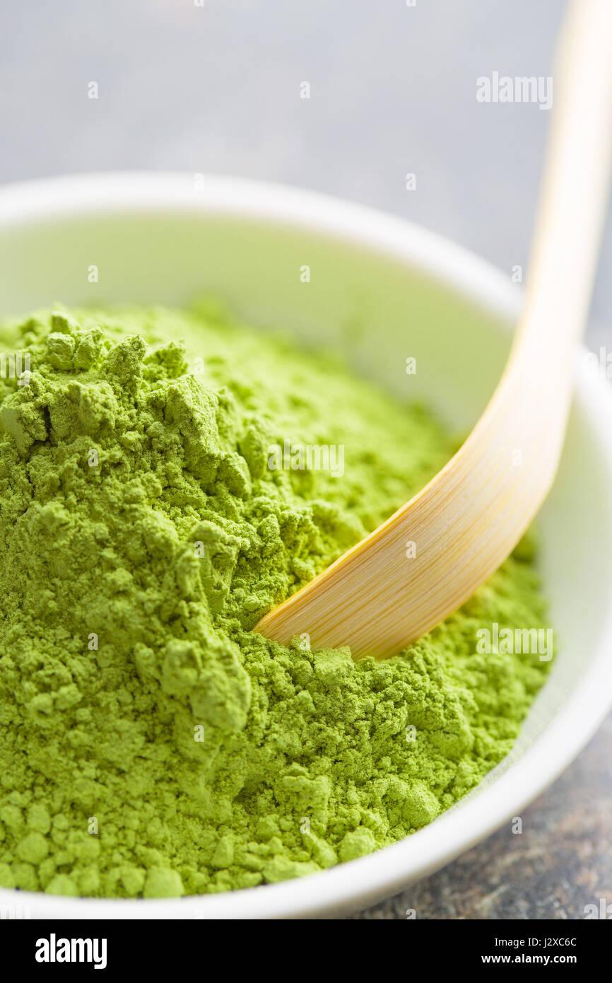 Green matcha tea powder in bowl. - Stock Image