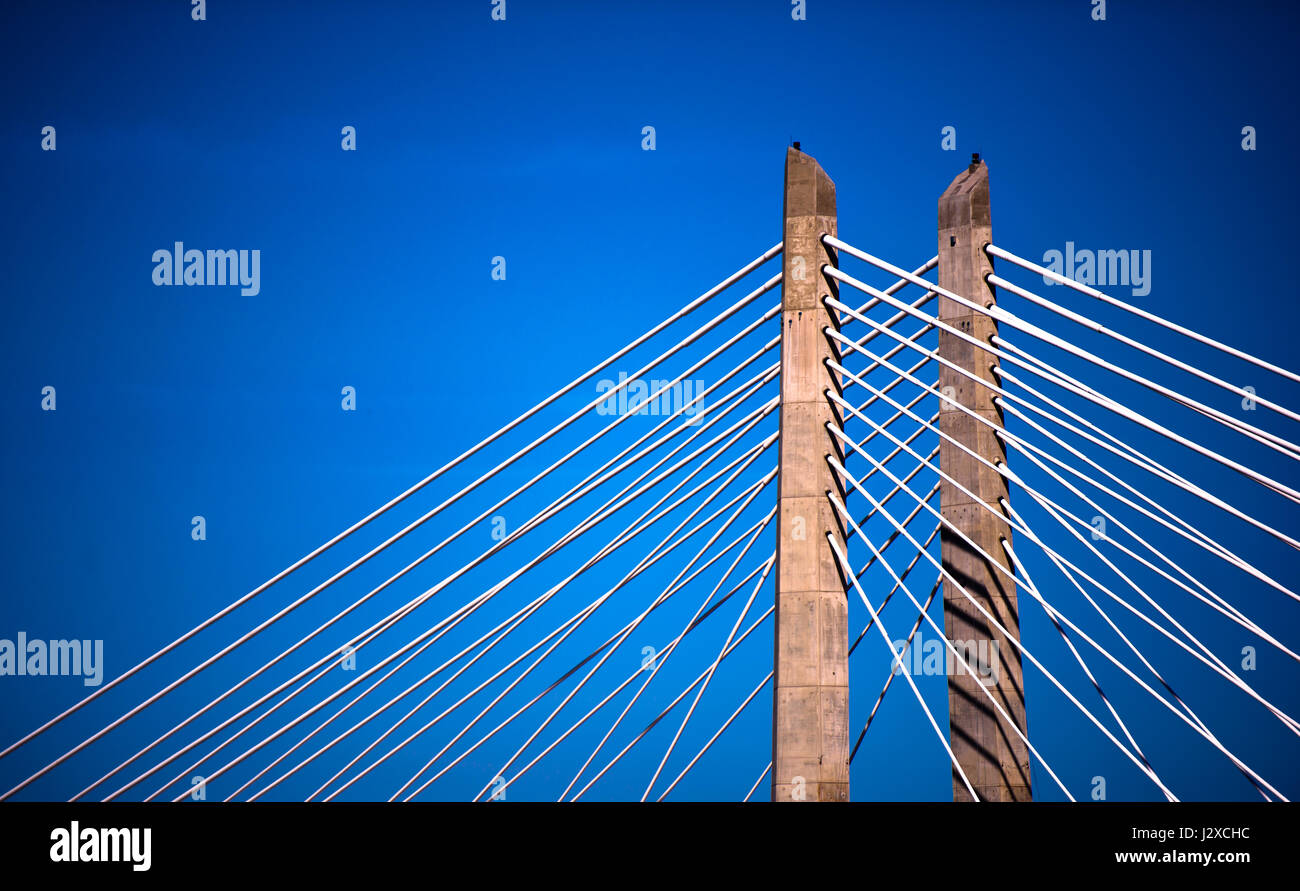 Rope suspension bridge stretching with two concrete supports columns through which the cable support structure of - Stock Image