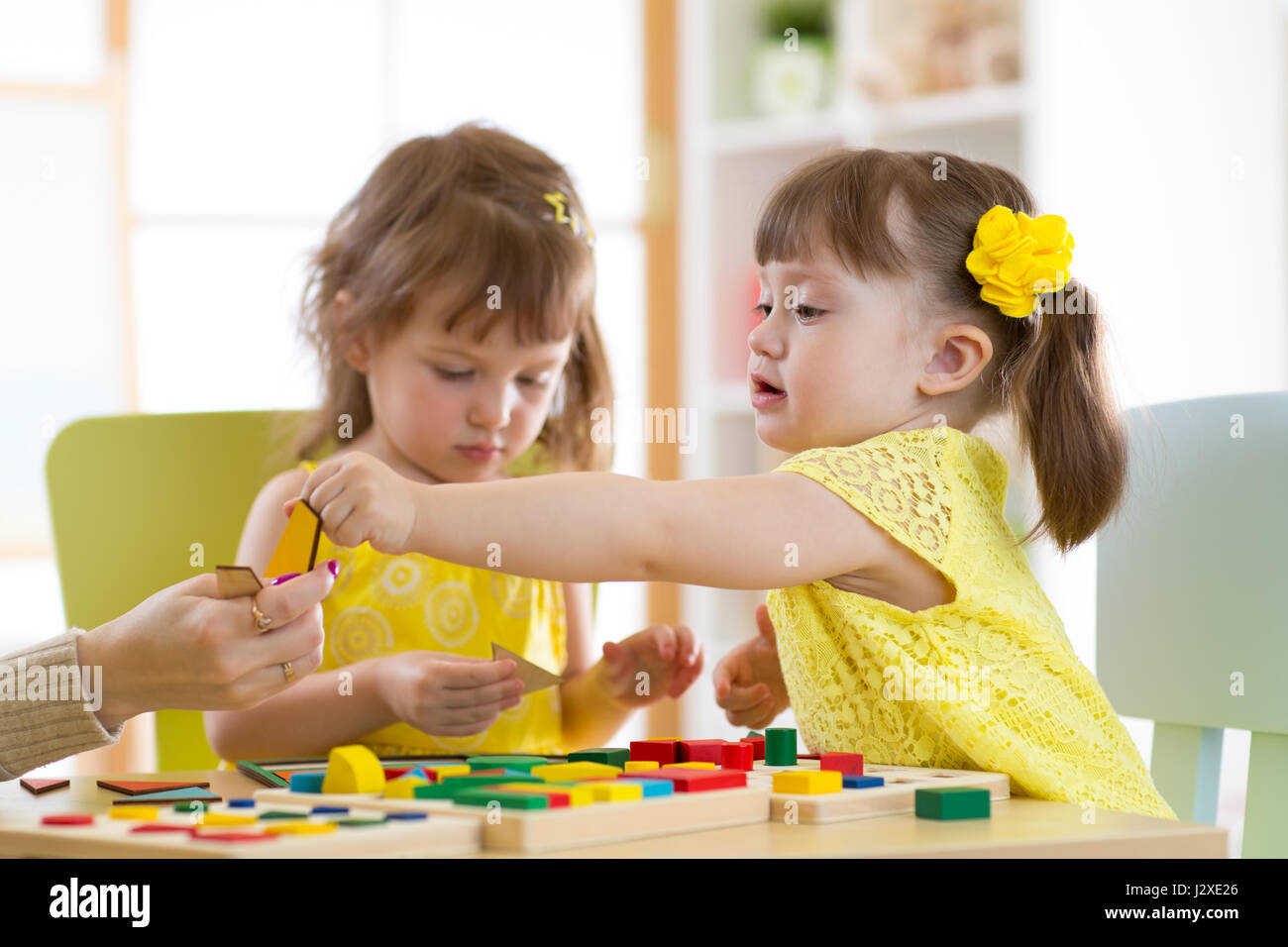 Preschool teacher and children playing with educational sorter toys in classroom - Stock Image