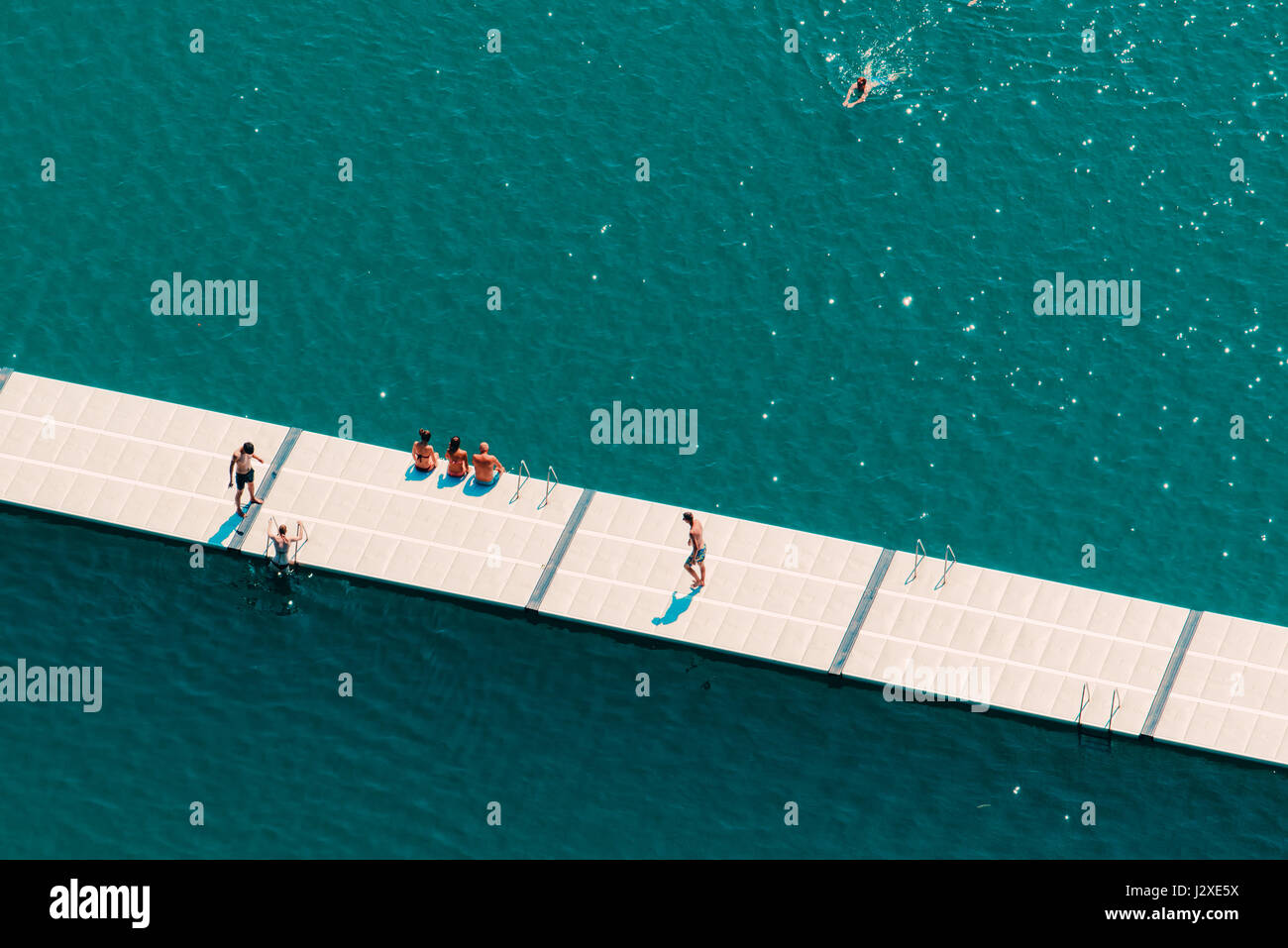 Unrecognizable people enjoying hot summer afternoon on lake Bled, aerial view of leisure and recreational activity - Stock Image