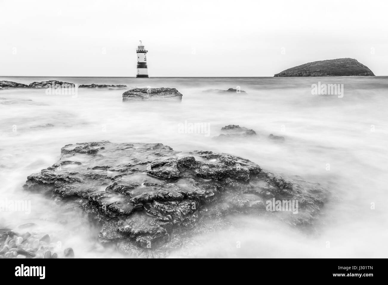 Trwyn Du or Penmon Lighthouse between Dinmor Point near Penmon and Ynys Seriol, or Puffin Island, at the eastern Stock Photo