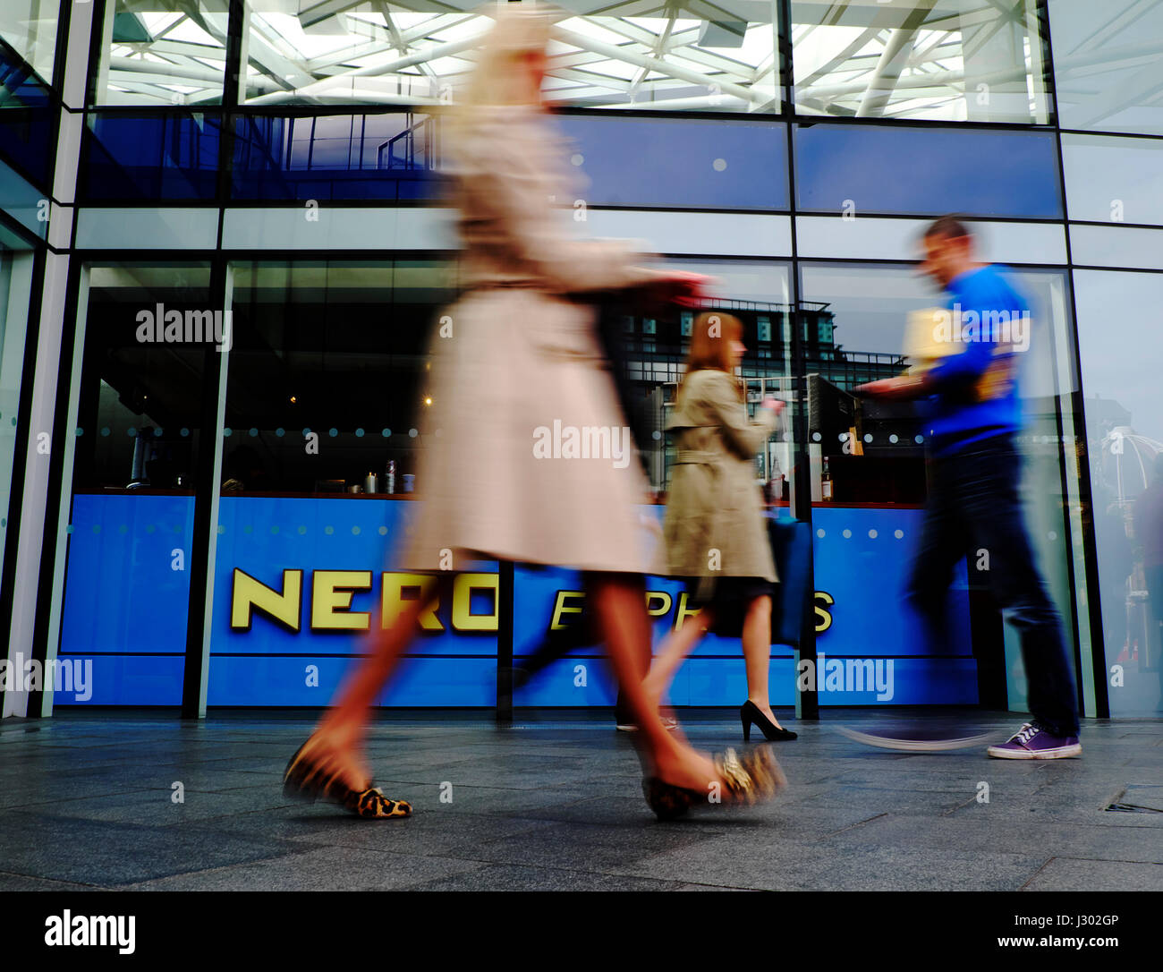 Commuters walk past a branch of Caffe Nero at Kings Cross Station in London - Stock Image
