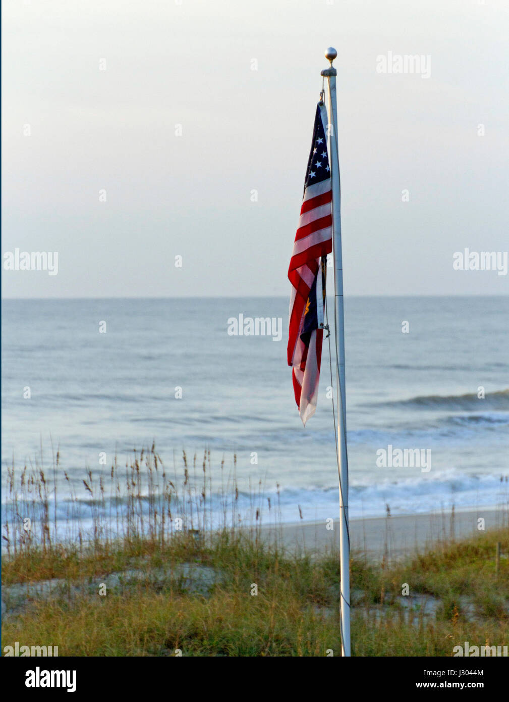 A deflated American flag hanging limply on a stiff flagpole by a dispirited seeming and dull looking Shining Sea - Stock Image