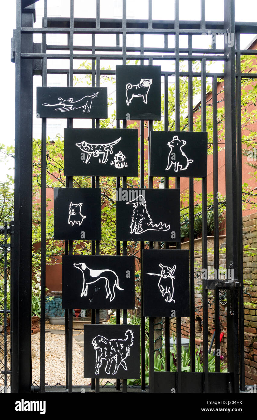 Charming black and white illustrations of dogs on the entrance gate of a Soho dog run in New York City - Stock Image