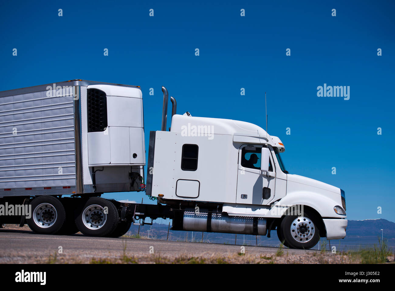 Big white truck with a trailer and a refrigeration unit on the road of the highway against the blue clear sky side view draws all the outlines