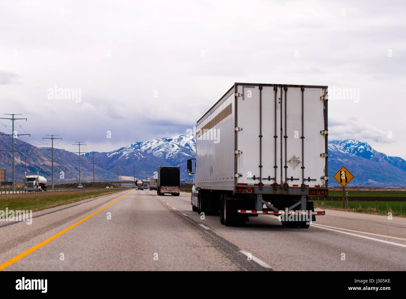 Picturesque straight multilane highway with a dividing strip oncoming traffic flows with a semi trucks and trailers - Stock Image