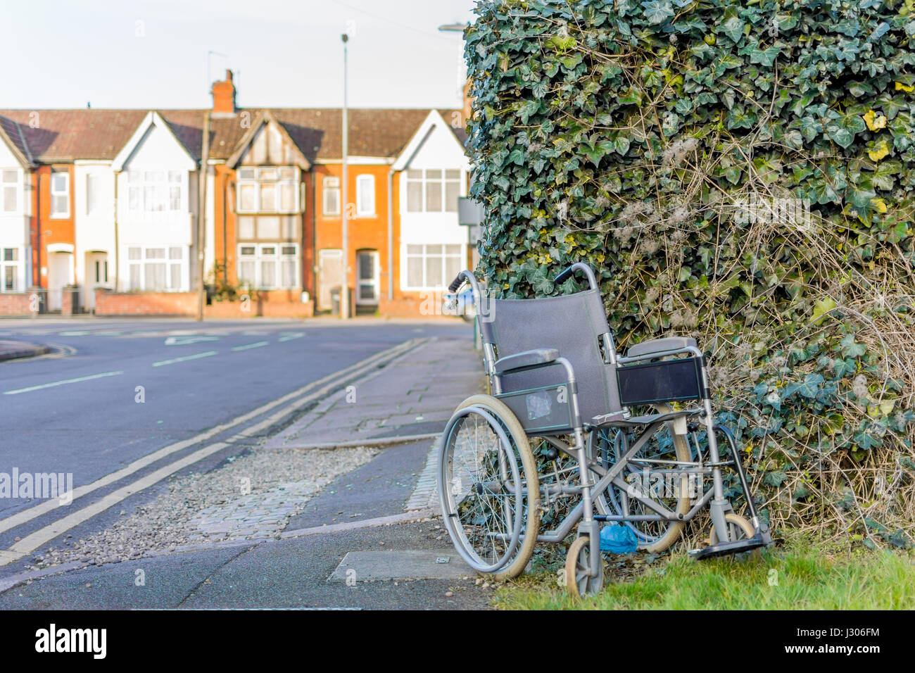 Abandoned wheelchair with cigarette packet on England street. - Stock Image