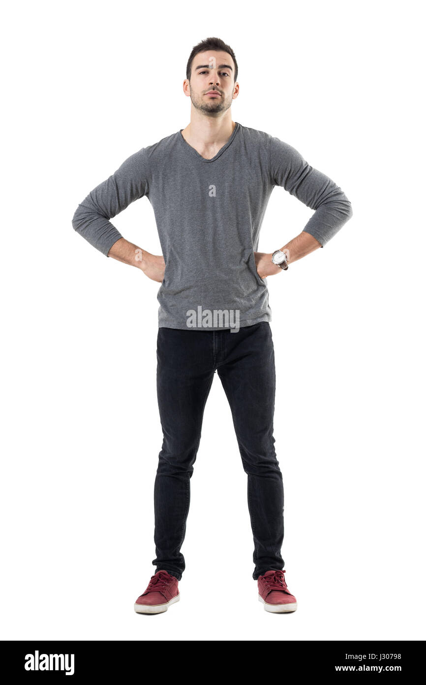 Suspicious distrustful man with hands on hips looking at camera. Full body length portrait isolated over white studio - Stock Image