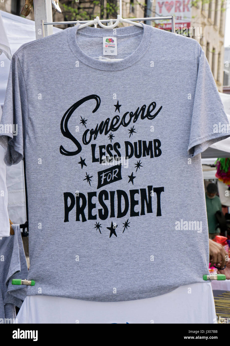 A tee shirt ridiculing President Donald Trump for sale at the Eighth Avenue Street Fair in the Chelsea section of - Stock Image