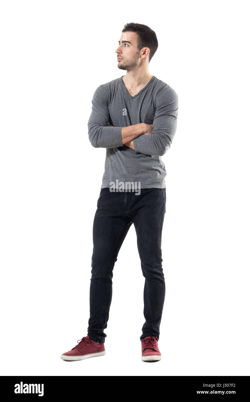 24a78d44e19 Handsome young casual man with crossed hands looking away. Full body length  portrait isolated over white studio background.