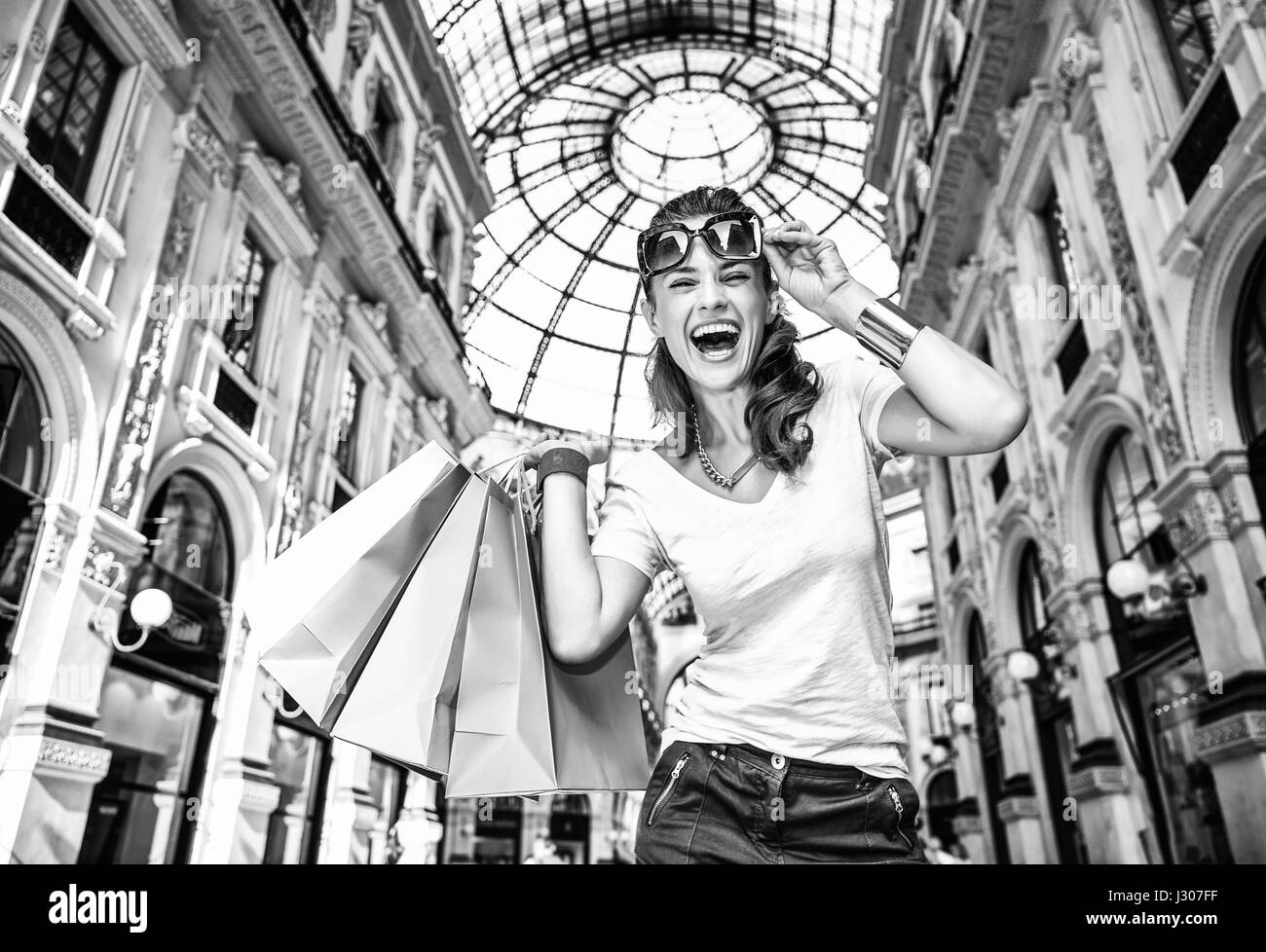 Discover most unexpected trends in Milan. Portrait of smiling fashion woman with eyeglasses and colorful shopping - Stock Image