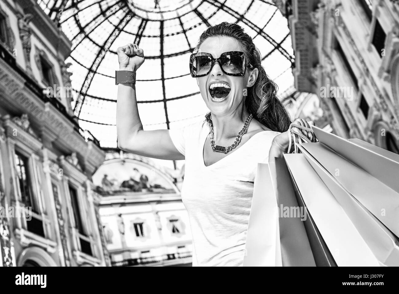 Discover most unexpected trends in Milan. Happy fashion woman in eyeglasses with colorful shopping bags in Galleria - Stock Image