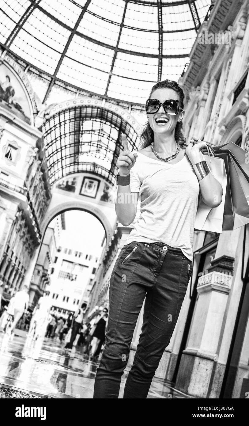 Discover most unexpected trends in Milan. Full length portrait of happy fashion woman in eyeglasses with colorful - Stock Image