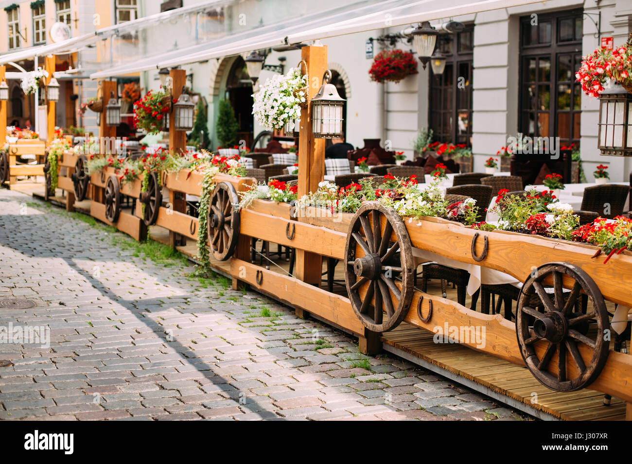 Exterior Of Cozy Outdoor Street Cafe In Retro Rural Rustic Style On Wooden Wall Or Restaurant Hanging Wheels From Peasants Carts