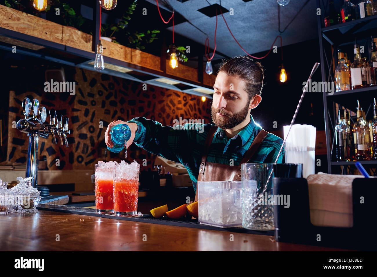 The barman with a beard makes  cocktail at  bar - Stock Image