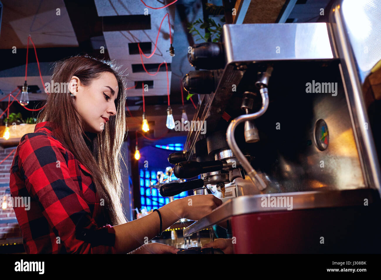 Bartender girl is making coffee in a bar - Stock Image