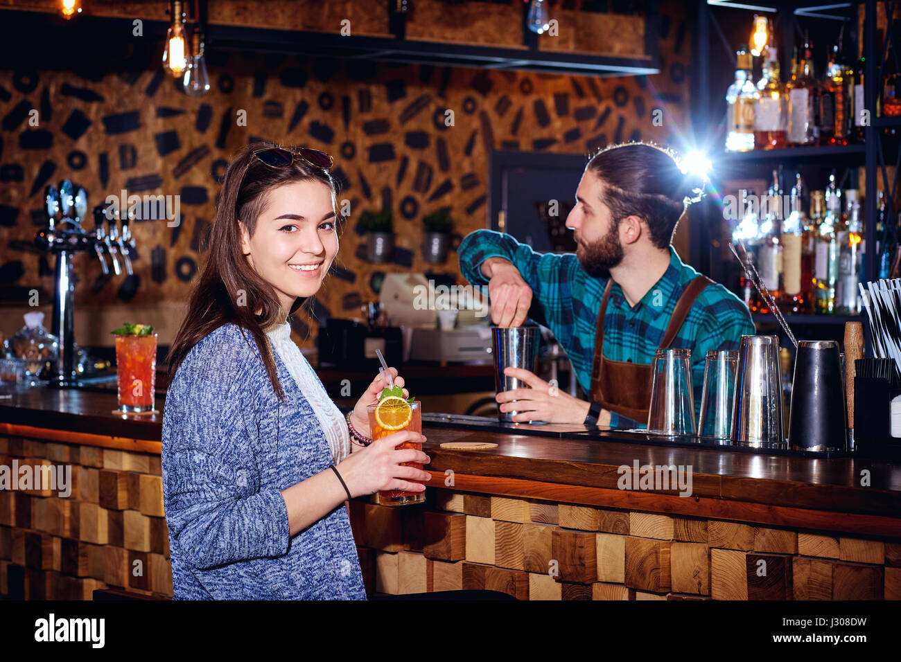 A girl with  cocktail smiles behind counter at the bar - Stock Image