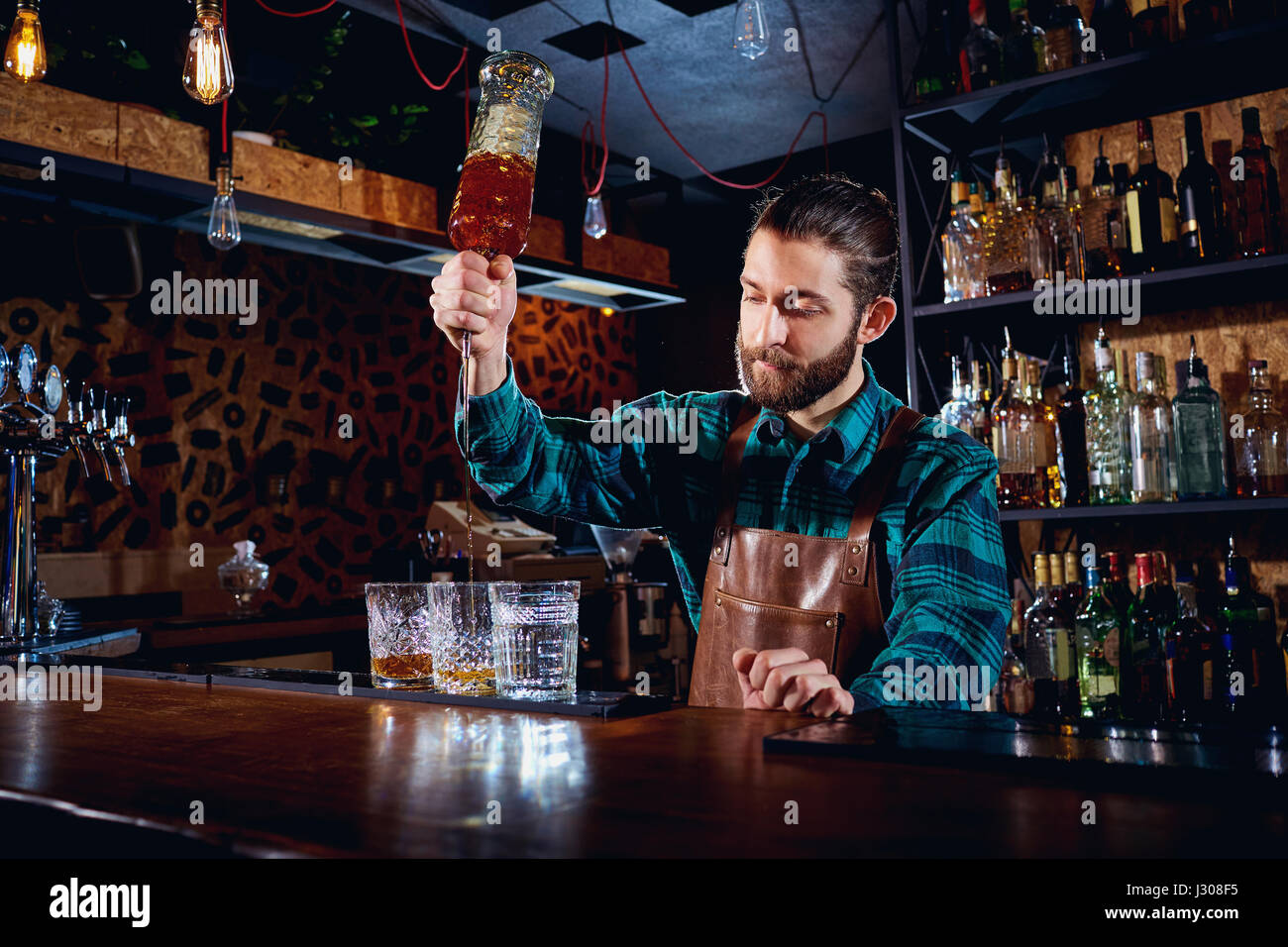 The barman with a beard pours alcohol into glasses in a bar - Stock Image