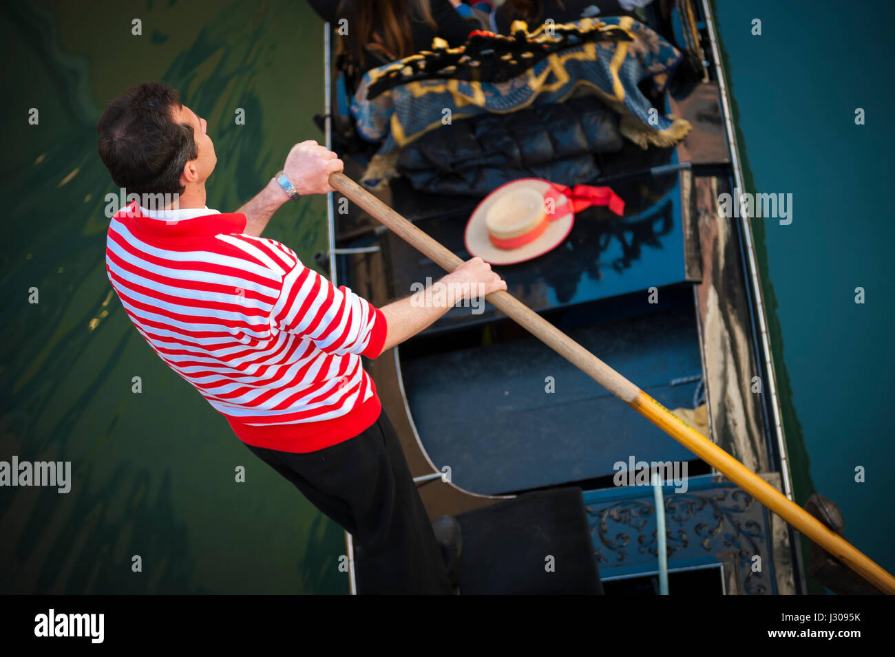 VENICE - APRIL 23, 2013: Venetian gondolier in traditional red and white striped shirt punts his gondola under a - Stock Image