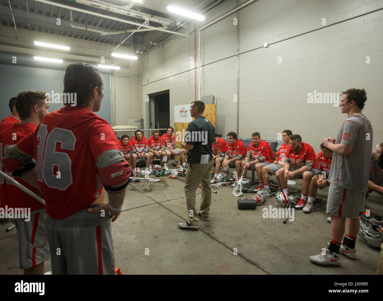 Head coach of the Ohio State lacrosse team speaking to players at halftime at a match against Rutgers Universiiy - Stock Image