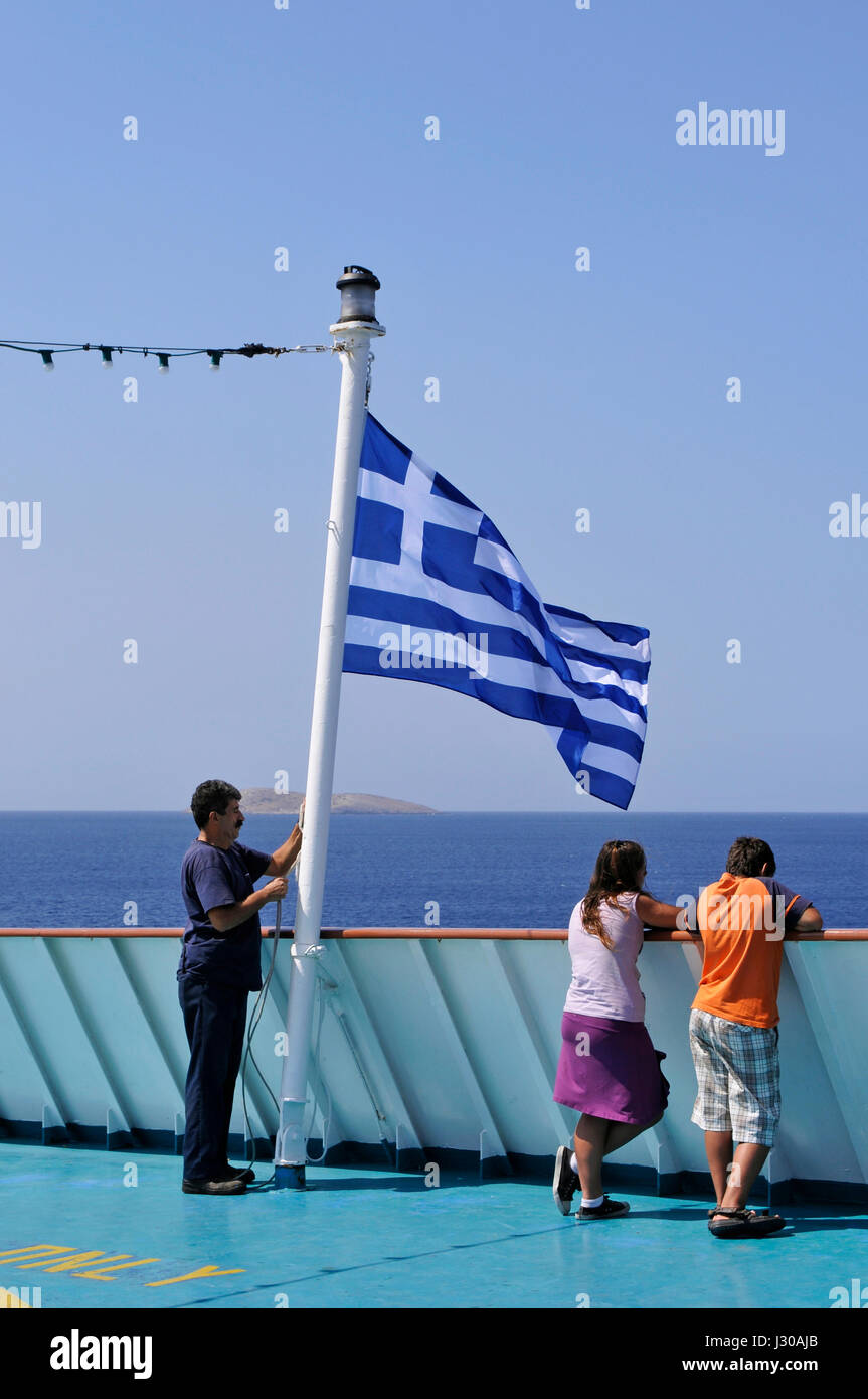 crew raising greek flag on board of a ferry Stock Photo