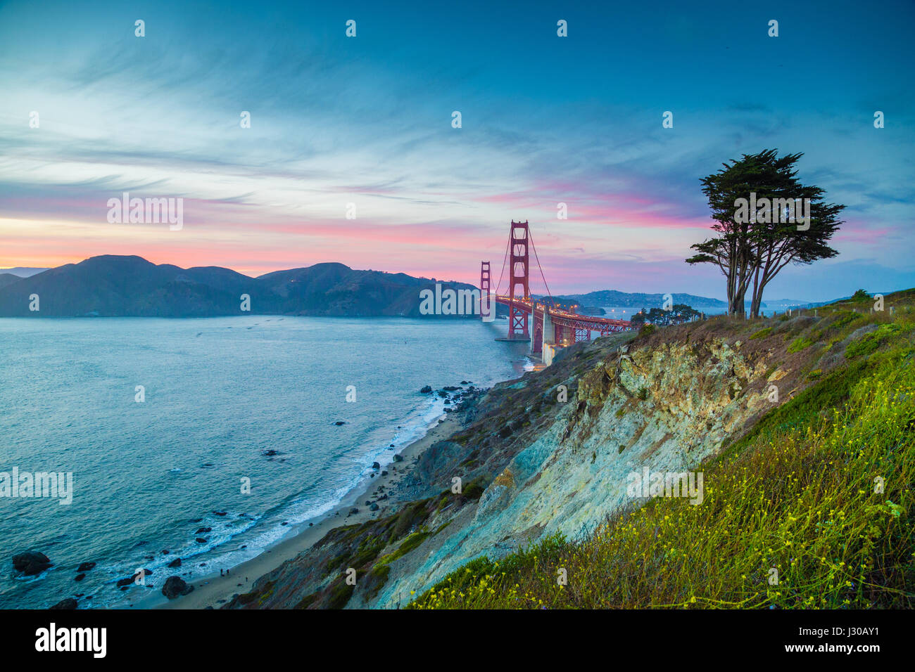 Classic panorama view of famous Golden Gate Bridge seen from scenic Baker Beach in beautiful post sunset twilight - Stock Image