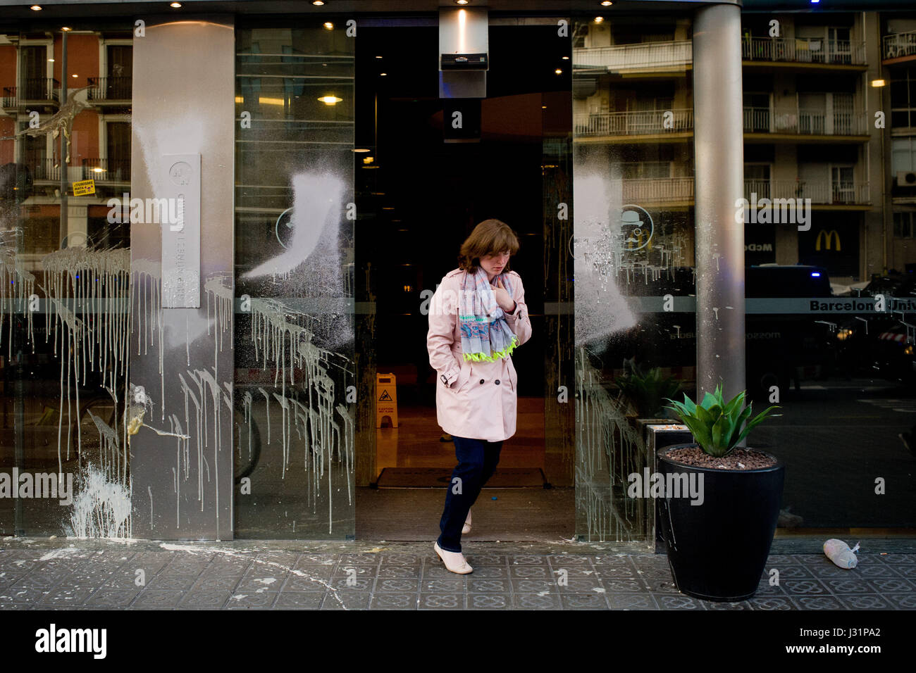 May 1, 2017 - Barcelona, Catalonia, Spain - A woman leaves a vandalized hotel door entrance during a May Day anti - Stock Image