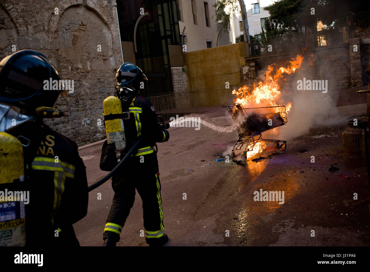 May 1, 2017 - Barcelona, Catalonia, Spain - Firefighters extinguish a burning shopping trolley during a May Day - Stock Image