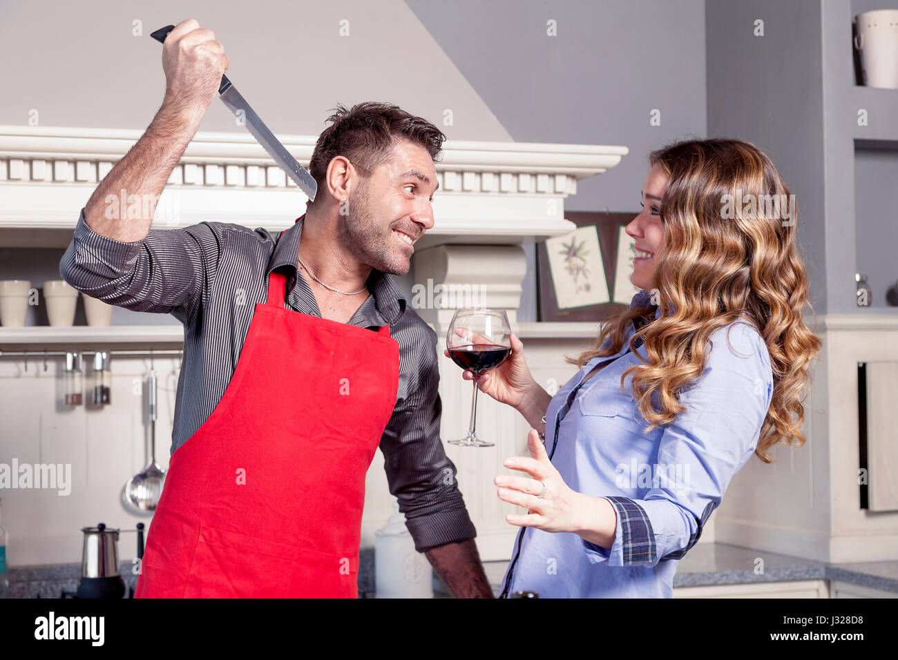 Young husband jokes with his wife in the kitchen with a knife