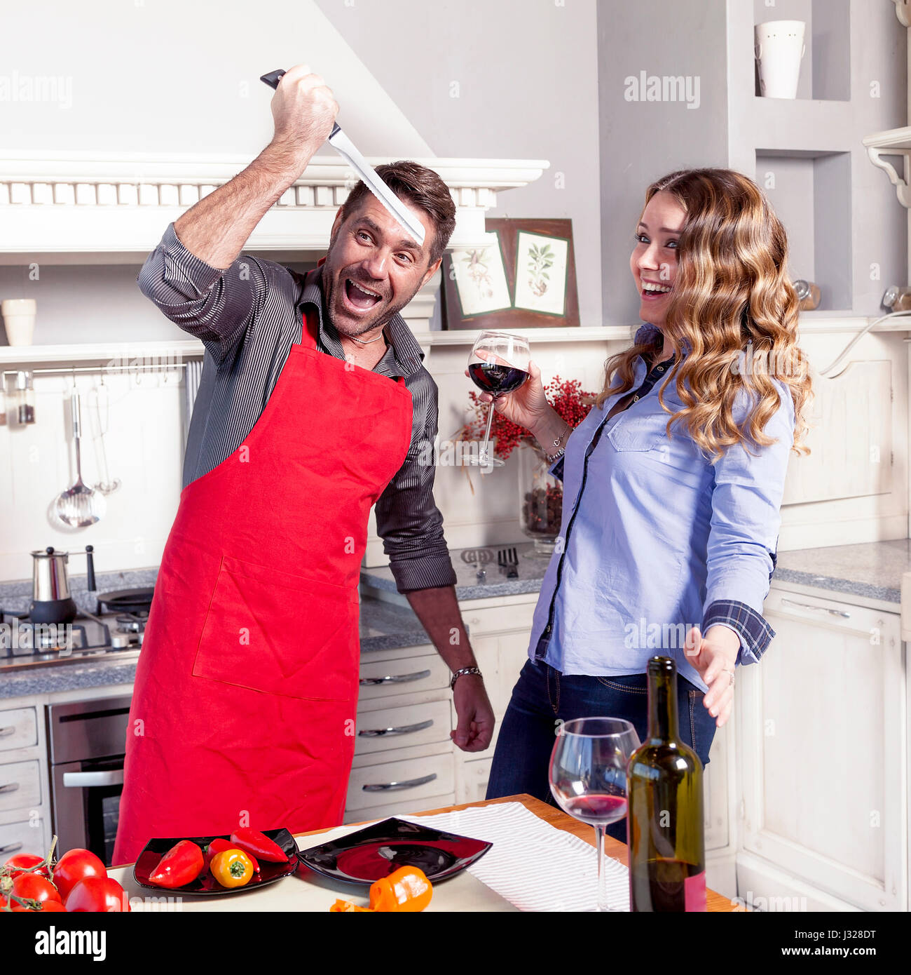 young husband jokes with his wife in the kitchen with a knife - Stock Image